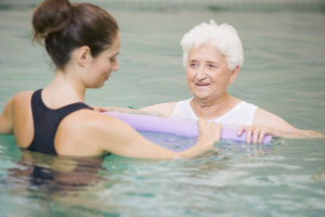 Therapist and senior patient in hydro pool