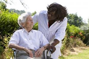 caregiver talking to senior women outdoors